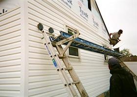 Guy working on house siding
