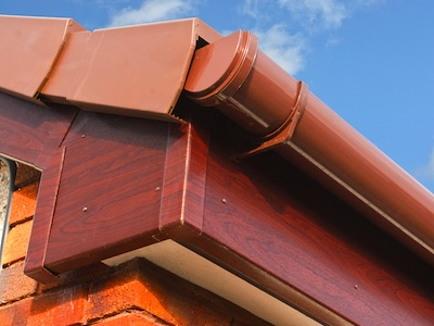 close up of Brown wood effect PVCu or plastic soffit fascia and guttering on modern new build residential property