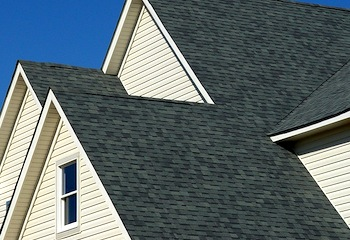 Residential house composition shingle roof line with multiple gables over blue sky