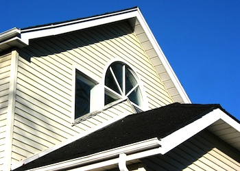 fragment of a house with gutters on with bright blue sky