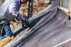 Roofer with a nail gun fixing a roof